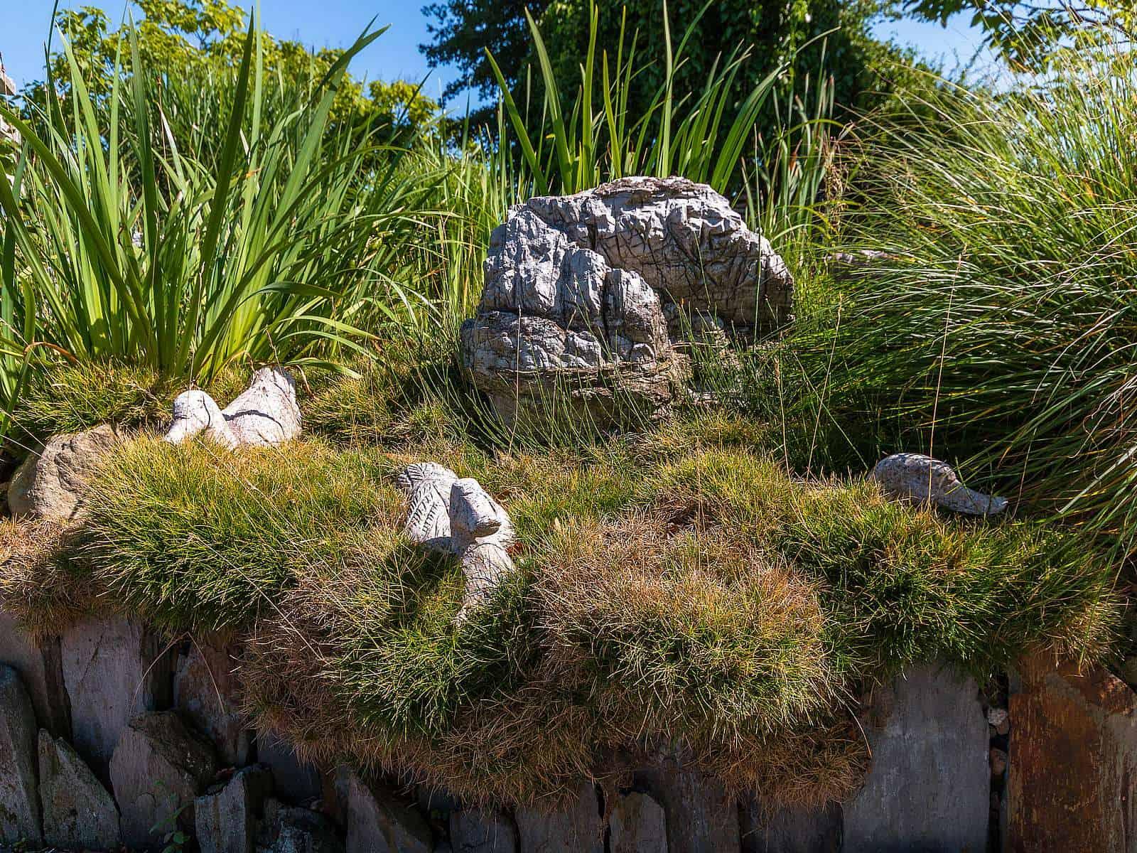 Steingarten im Grün mit Enten und Chinafelsen.
