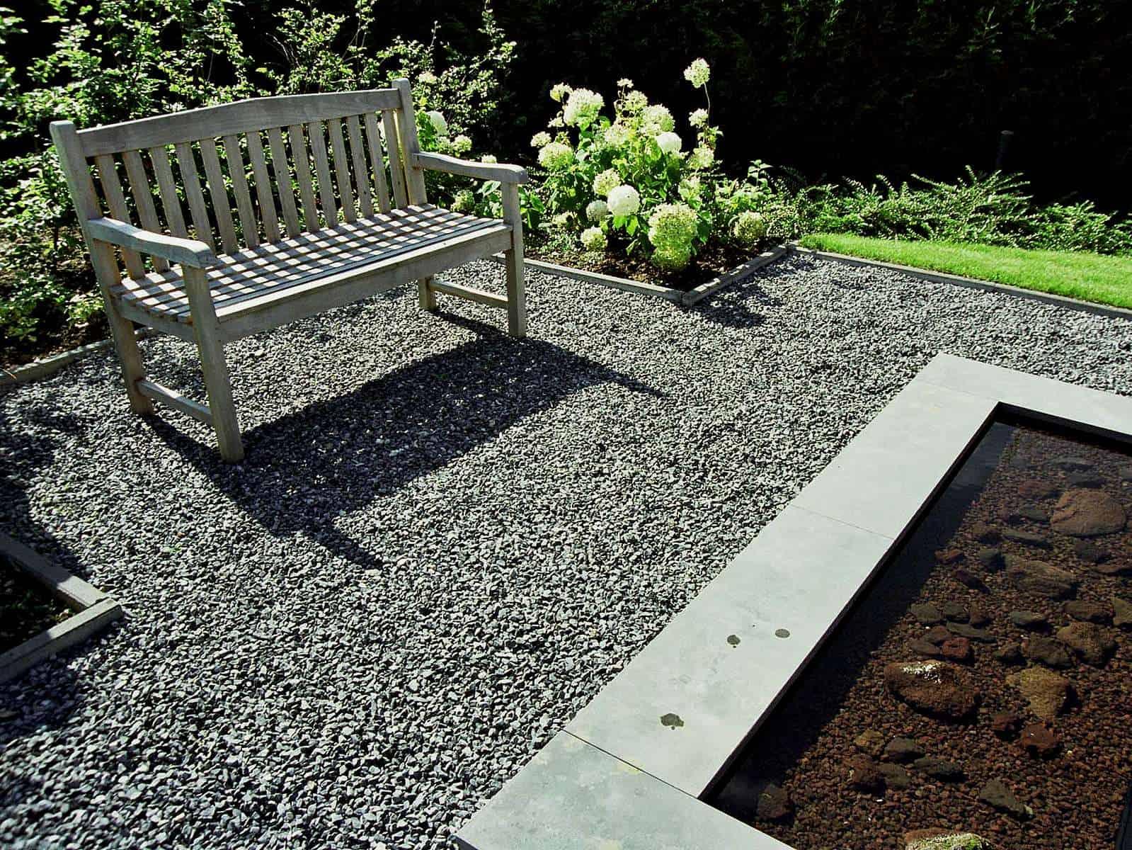 Splittfläche mit Sitzbank am Wasser. Einfache, moderne und grandlinige Gartengestaltung mit Naturstein.