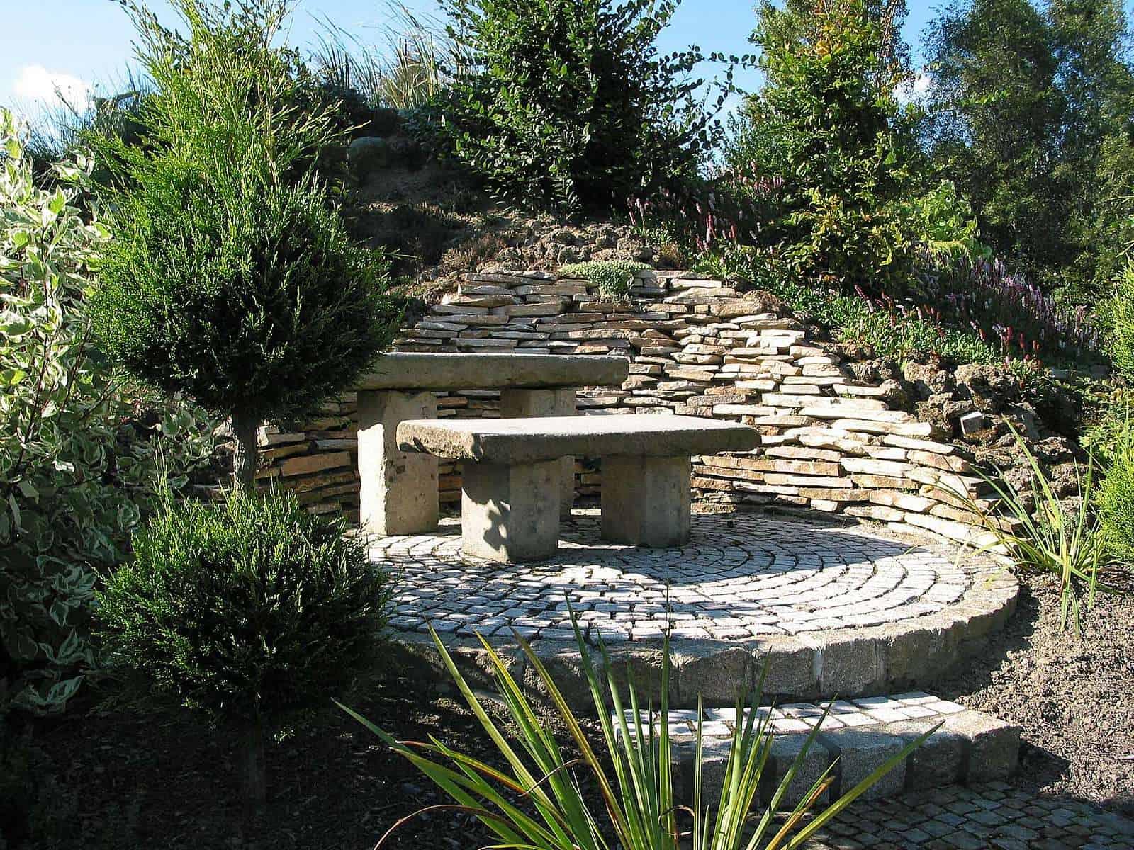 Trockenmauer aus beigem Kalkfels und Travertinpflaster. Sitzgruppe aus Naturstein.